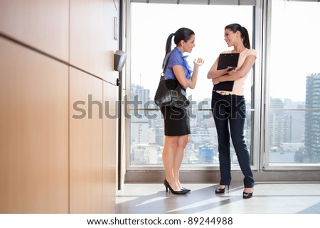 Full length of two female executives talking to each other in office