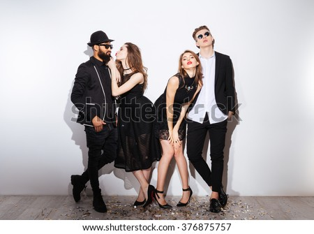 Full length of two happy drunk young couples standing over white background