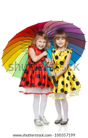 Full length of two little girls standing under umbrella over white background