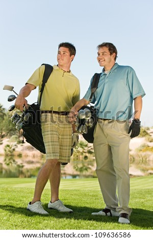 Full length of two male golfers carrying golf bags on golf course