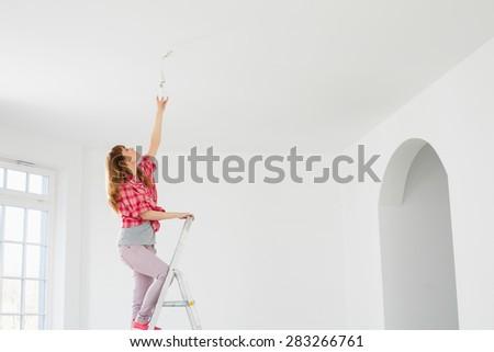 Full-length of woman on ladder fitting light bulb in new house
