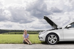 Full length of worried businesswoman sitting by broken down car at countryside