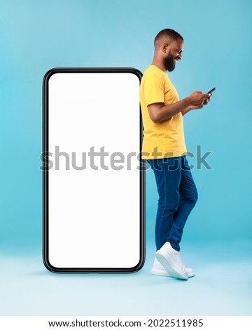 Full length of young Afro guy using cellphone while leaning on giant mobile phone with empty white screen, blue studio background. Mockup for app or website, space for advertisement
