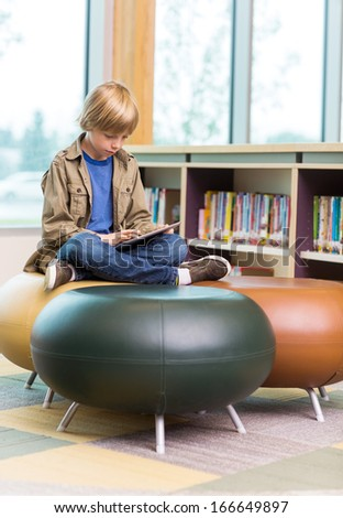 Full length of young boy using digital tablet on seat in school library