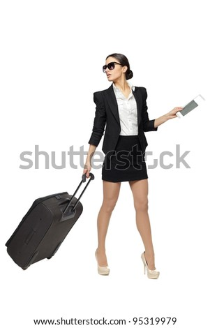 Full length of young business woman pulling the travel bag, isolated on white background