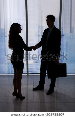 Full length of young businessman and businesswoman shaking hands in office