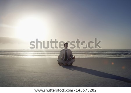 Full length of young businessman meditating in lotus position on beach