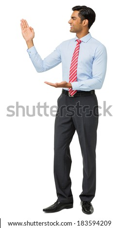 Full length of young businessman showing an invisible product against white background. Vertical shot.