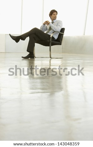 Full length of young businessman sitting on armchair in empty conference room