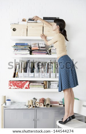 Full length of young businesswoman reaching for shelf in home office