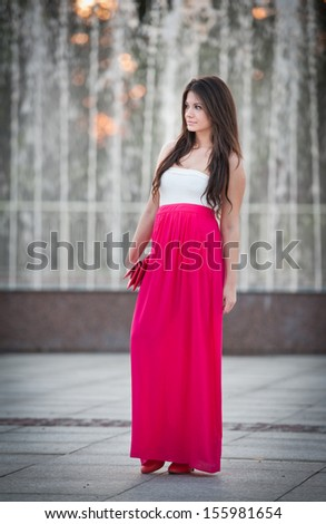 Full length of young caucasian female with long red skirt standing near fountain.Romantic portrait of the woman.