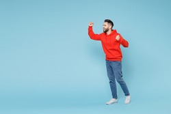 Full length of young caucasian happy bearded overjoyed excited man 20s in casual red orange hoodie do winner gesture clenching fist celebrate look aside isolated on blue background studio portrait