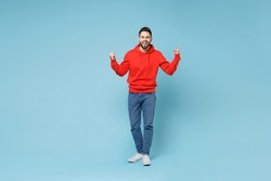 Full length of young caucasian happy bearded overjoyed excited man 20s in casual red orange hoodie doing winner gesture clenching fist celebrating isolated on blue color background studio portrait