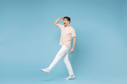 Full length of young caucasian happy excited successful student man 20s in beige t-shirt white pants holding hand at forehead looking far away distance isolated on blue colorbackground studio portrait