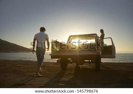 Full length of young couple by pick-up truck parked on beach - stock photo