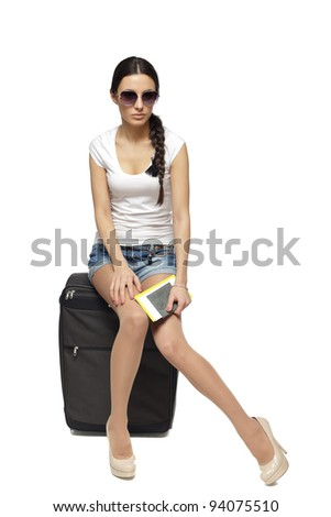 Full  length of young female in casual sitting on her black travel bag and holding the tickets with passport isolated on white background