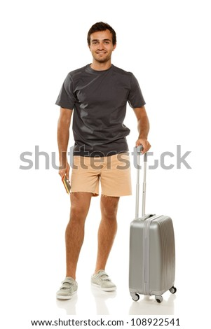 Full length of young male tourist standing with suitcase, holding tickets and passport, isolated on white background
