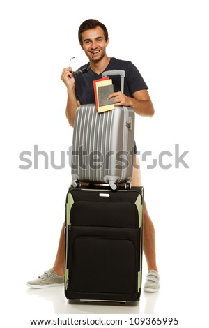 Full length of young tanned male standing with suitcases, holding tickets and passport, isolated on white background