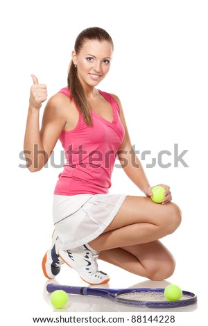 Full length of young tennis woman sitting in the squatting position and showing thumb up sign, on white background - stock photo