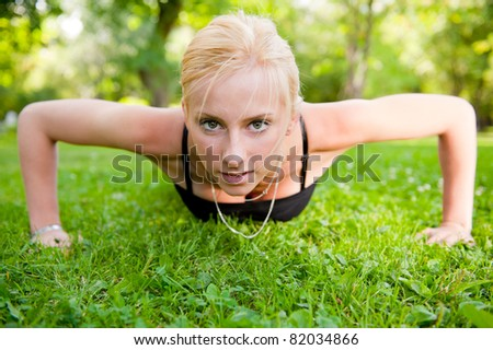 Full length of young woman doing pushups on green grass at summer park