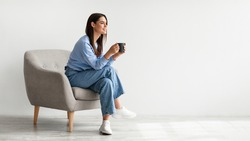 Full length of young woman drinking hot coffee in cozy armchair against white studio wall, banner design with free space. Peaceful lady having relaxing day, chilling on lazy morning