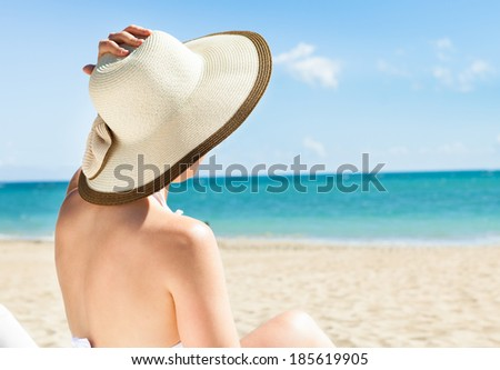 Full length of young woman in bikini enjoying the ocean view while relaxing on beach chair #185619905