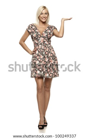 Full length of young woman showing a product - empty copy space on the open hand palms, over white background - stock photo