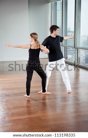 Full length of young yoga partners exercising at gym