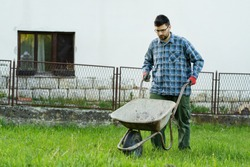 Full length on man with pushcart on the field - Caucasian male adult using handcart while working around his house in day - copy space