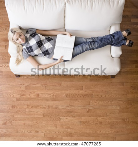 Full length overhead view of woman reclining on white couch with a book, as she looks up at the camera. Square format.