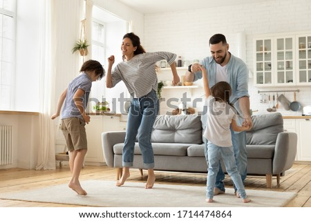 Full length overjoyed family of four jumping to music in modern studio living room. Excited young married couple dancing with playful little children siblings, spending active free time at home.