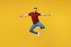 Full length overjoyed fun happy young man wear red t-shirt casual clothes jump high with outstretched hands isolated on plain yellow color wall background studio portrait. People lifestyle concept.