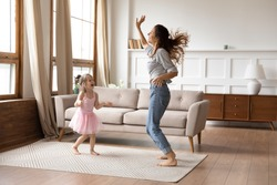 Full length overjoyed little preschool child girl in princess wear spending active weekend time with happy young mother. Crazy energetic family of two dancing together to music in living room.