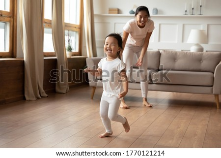 Full length overjoyed little preschool cute vietnamese ethnic baby girl running barefoot on warm floor, having fun playing with energetic young asian mother or nanny, leisure daycare activity.