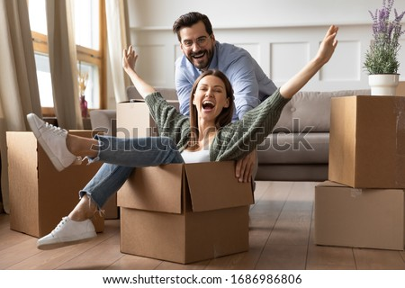 Full length overjoyed young bearded man in glasses pushing laughing wife in carton box. Energetic happy woman sitting in carboard container, having fun with smiling husband in new apartment house.