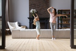 Full length overjoyed young mother dancing to favorite energetic music with little cute adorable smiling daughter in living room. Happy family of two enjoying active time on weekend at home.