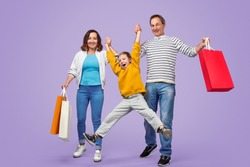 Full length parents with paper bags swinging cheerful boy during shopping against purple background