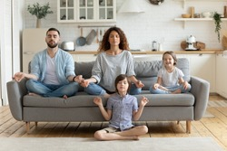 Full length peaceful calm couple practicing yoga exercises with small children in studio living room. Mindful little boy sitting on floor in lotus pose while parents relaxing on sofa with sister.