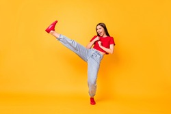 Full length photo focused girl practicing kicks raise leg exercise wear red crop top jeans isolated yellow color background