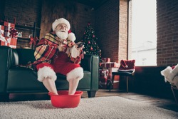 Full length photo funny grey white beard hair santa claus sit couch rest x-mas delivery present watch tv switch remote control soak hot water feet wear headwear in house indoors christmas tree