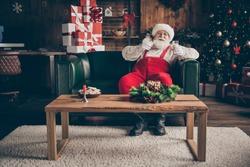 Full length photo jolly grey beard santa claus sit comfort couch enjoy watch x-mas christmas movie fairytale drink milk eat cookies wear red cap headwear in noel advent orament house indoors