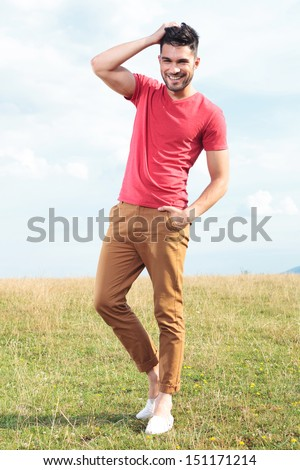 full length photo of a casual young man outdoor standing with a hand in his pocket and passing the other through his hair while smiling for the camera