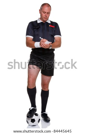 Full length photo of a football or soccer referee with ball writing in his report book, isolated on a white background.