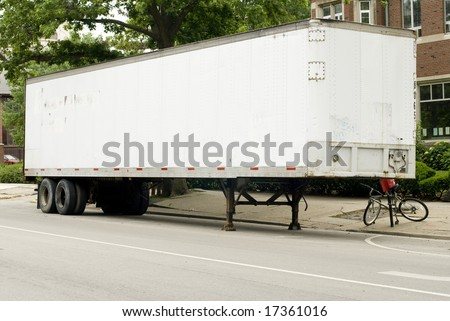 Full length photo of a white semi-truck trailer