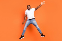 Full length photo of active cheerful afro american man jump up good mood excited isolated on orange color background
