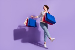 Full length photo of adorable young lady dressed casual clothes dancing holding colorful bargains isolated purple color background