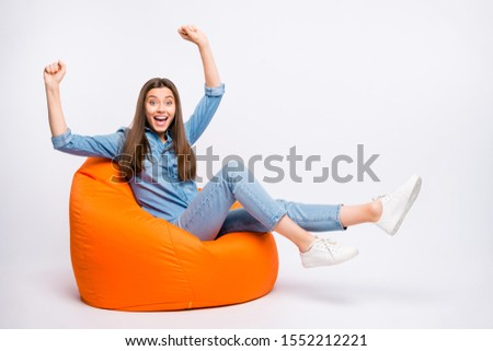 Full length  photo of amazed crazy girl sit bag chair  watch sport competition victory impressed scream wow omg raise fists wear casual style outfit isolated over white color background