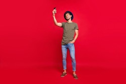 Full length photo of amazing guy holding telephone making selfies wear casual outfit isolated on red background