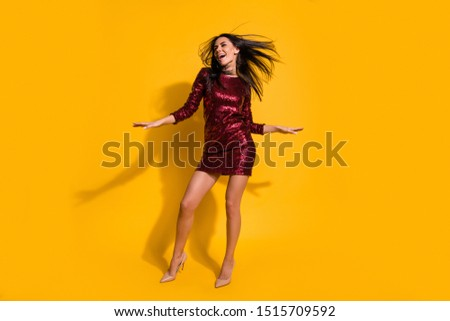 Full length photo of amazing lady with flying hairdo and perfect slim shapes dancing at disco party wear short shine red dress isolated yellow color background