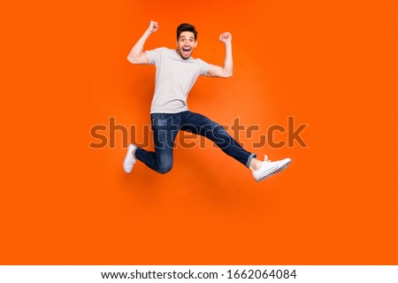 Full length photo of attractive crazy guy jump high supporting favorite football team match game goal wear striped t-shirt jeans shoes isolated bright orange color background
